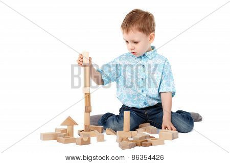 Little Boy Playing With Wooden Designer On The Floor