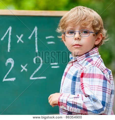Preschool Kid Boy With Glasses At Blackboard Practicing Mathematics