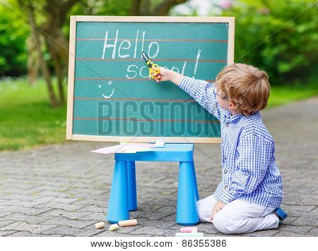 Cute Little Kid Boy With Glasses At Blackboard Practicing Writing
