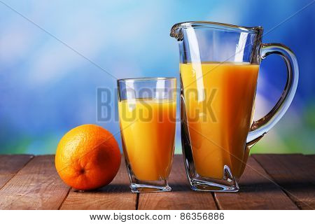 Glass and pitcher of orange juice on wooden table on natural background