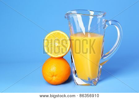 Glass pitcher of orange juice on blue background