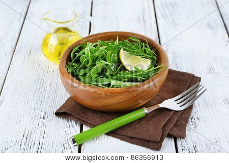 Bowl of green salad and sliced lemon on wooden background