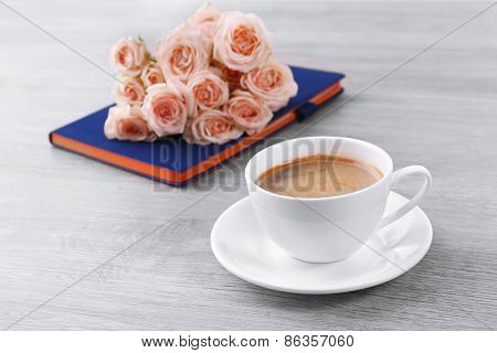 Fresh roses with diary and cup of coffee on wooden background