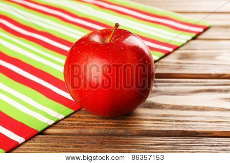 Apple  with napkin on wooden table, closeup
