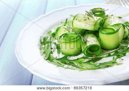 Plate of green salad with cucumber, arugula and rosemary on wooden table, closeup