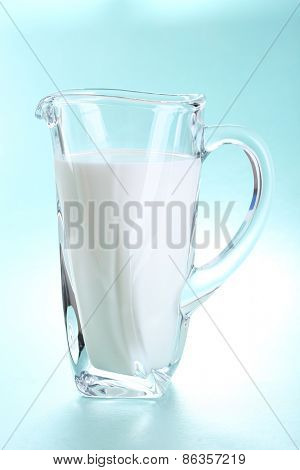 Pitcher of milk on blue background