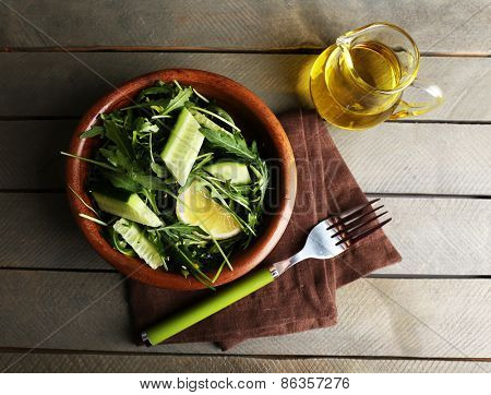 Bowl of green salad and sliced lemon on wooden table, top view