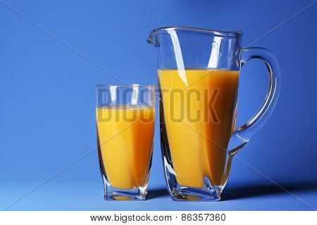 Glass and pitcher of orange juice on blue background
