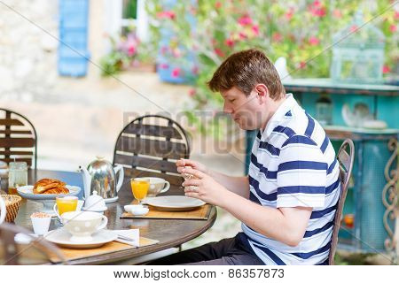 Young Man Having Breakfast Outside In Summer With Various Jams, Bread, Coffee