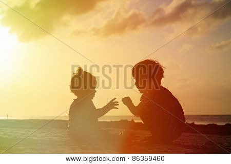 little boy and toddler girl playing at sunset