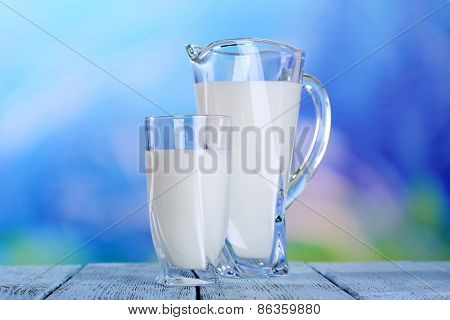 Pitcher and glass of milk on wooden table on natural background