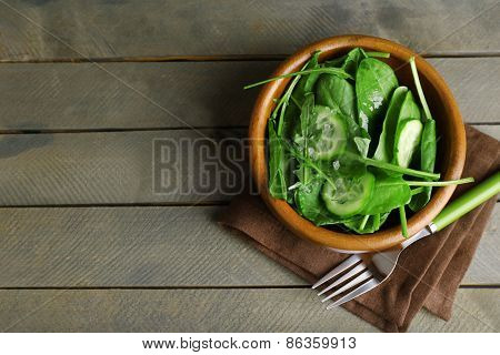 Green salad in bowl on wooden table, top view