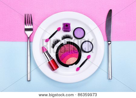 Makeup accessories on plate on colorful background