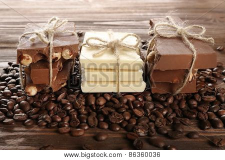 Stack of tied chocolate with coffee beans on wooden table, closeup