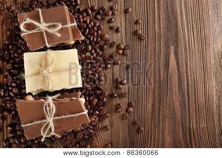 Stack of tied chocolate with coffee beans on wooden table, top view
