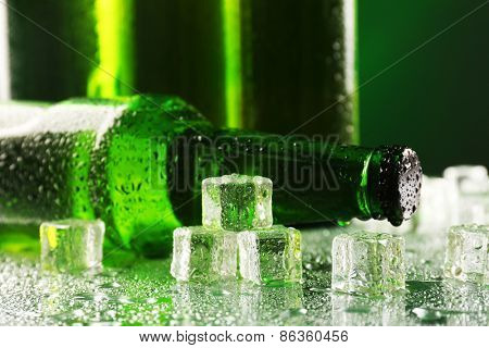 Glass bottles of beer with ice cubes on wet table on dark background