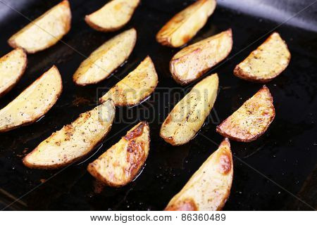 Baked potatoes with spices on pan close up