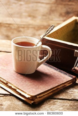 Old wooden suitcase with old books and tea cup on wooden background