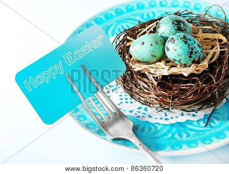 Easter table setting with card and Easter eggs, close up