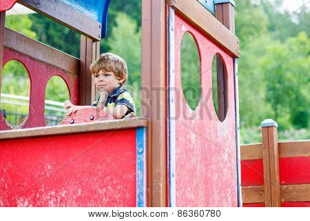 Child Boy Pretends Driving An Imaginary Car On Kids Playground