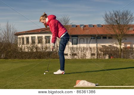 Young Female Golfer Putting Ball Towards Hole