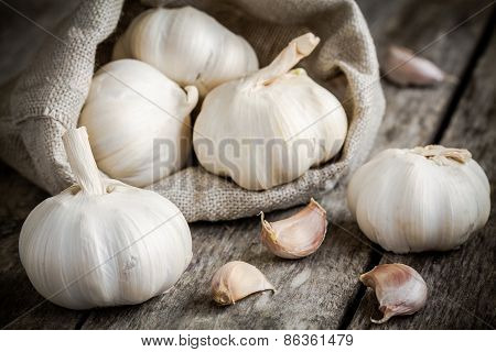 Organic Garlics In The Bag On A Wooden Table