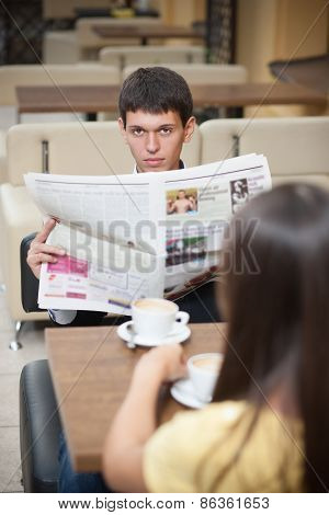 Young man with newspaper across table with cup of coffee