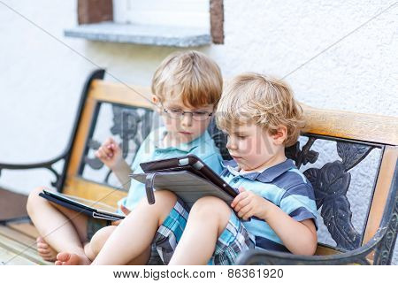 Two Happy Twins Boys Friends Holding Tablet Pc, Outdoors.