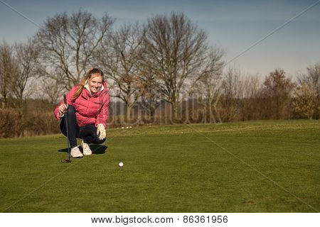 Female Golfer Lining Up A Putt