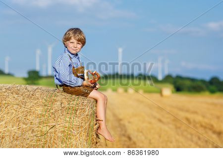 Funny Little Kid Boy Sitting On Hay Stack  And Eating Pretzel