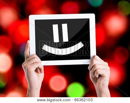 Tablet pc with text Smiley Face with bokeh background