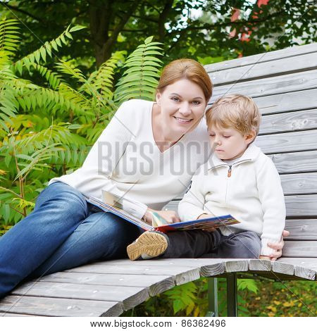 Little Boy And His Mother Sitting On Bench In Park And Reading Book