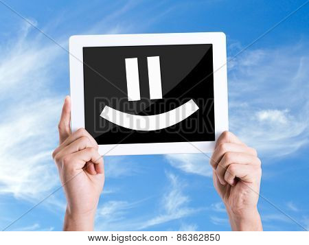 Tablet pc with text Smiley Face with sky background