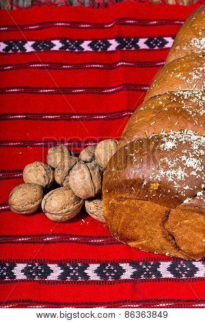 Romanian sponge cake and bunch of walnuts on red traditional tow