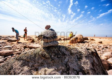 Pyramid Of The Old Stones On The Beach With The Sun Vacationers People