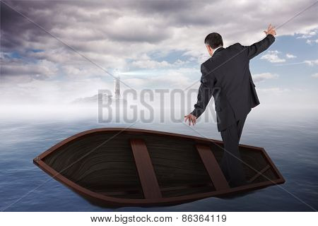 Businessman balancing in boat against calm sea with lighthouse