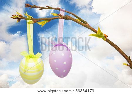 Hanging easter eggs against cross shape in the sky