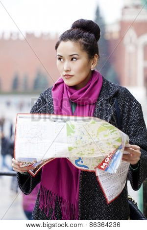 Young beautiful asian girl holding a tourist map of Moscow, Russia. The inscription on the tourist map:
