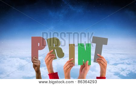 Hands showing print against white clouds under blue sky