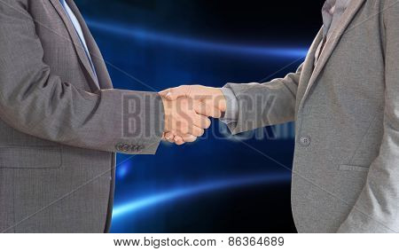 Close up on two businesspeople shaking hands against business online on digital screen