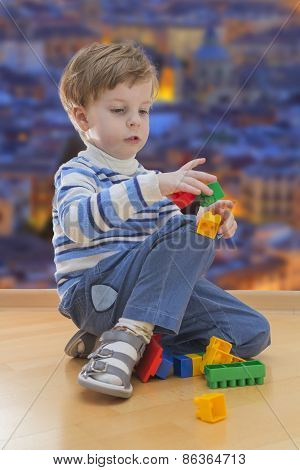 Boy playing with plastic construction with evening city in background