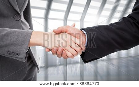 Close up of two businesspeople shaking their hands against room with large window looking on city