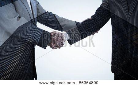 Handshake in agreement against skyscraper