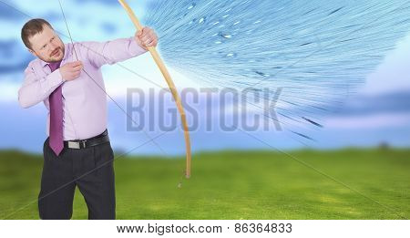 Businessman practicing archery with green field in background