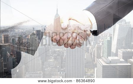 Handshake between two business people against city skyline