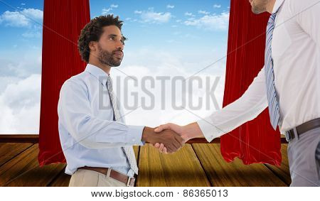 Young businessmen shaking hands in office against stage with red curtains