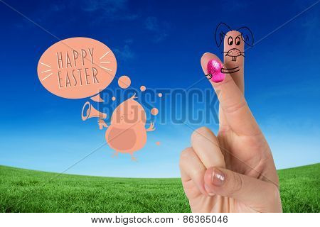 Fingers as easter bunny against green field under blue sky