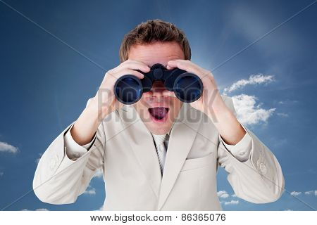 Positive businessman using binoculars against cloudy sky with sunshine