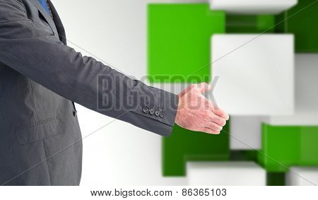 Businessman holding his hand out against green tile design