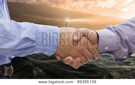 Two men shaking hands against stormy sea with lighthouse